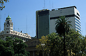 Buenos Aires, Argentina. Old and modern city centre buildings with palm trees of a plaza in front.