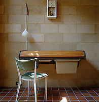 An Ernest Race design chair is teamed with a George Nelson roll-top desk against the breeze block wall of the study
