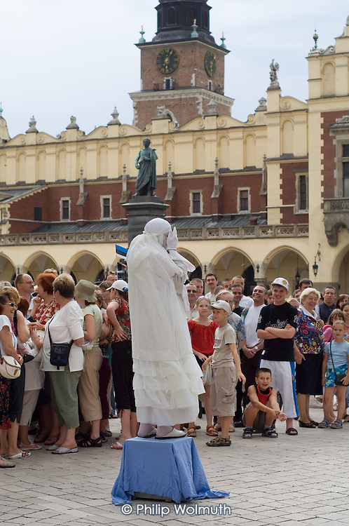 A mime artist performs to crowd of tourists in the medieval central square of Krakow (the Rynek Glowny).