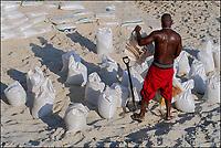 Homem negro com sacos de areia branco, Praia do Arpoador, Rio de Janeiro. 2019. Foto © Juca Martins