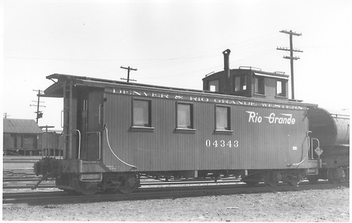 Side view of long caboose #04343, at Alamosa, flying herald.<br /> D&amp;RGW  Alamosa, CO  Taken by Perry, Otto C. - 4/1950