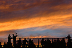Sport spectators in bleachers with silhouettes against sunset sky.