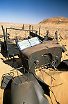 Africa, Libya, Fezzan. Temporary visitors evidence at the remains of one of three LRDG Chevrolet trucks in a valley of the Gebel Sherif mountains southwest of Kufra. During Second World War on January 31 1941 the Long Range Desert Group was attacked by the Italian Compagnie Sahariane. Libyen 1999/2000.<br /> <br />  --- No releases available. Automotive trademarks are the property of the trademark holder, authorization may be needed for some uses.<br /> <br />  --- INFO: The Long Range Desert Group (LRDG) was a reconnaissance and raiding unit of the British Army during the Second World War. Originally called the Long Range Patrol Unit (LRP), the unit was founded in Egypt in June 1940 by Major Ralph A. Bagnold. Bagnold was assisted by Captain Patrick Clayton and Captain William Shaw. At first the majority of the men were from New Zealand, but they were soon joined by Rhodesian and British volunteers, whereupon new sub-units were formed and the name was changed to the better-known Long Range Desert Group (LRDG).<br /> <br /> The LRDG vehicles were mainly two wheel drive, chosen because they were lighter and used less fuel than four wheel drive. They were stripped of all non-essentials, including doors, windscreens and roofs. They were fitted with a bigger radiator, a condenser system, built up leaf springs for the harsh terrain, wide, low pressure desert tyres, sand mats and channels etc. Initially the LRDG patrols were equipped with one CMP Ford 15 cwt F15 truck for the commander, while the rest of the patrol used up to 10 Chevrolet 30 cwt WB trucks.<br /> <br /> On 31 January 1941 'T' Patrol commanded by Captain Patrick Clayton was attacked by the Compagnia Autosahariana di Cufra, an Italian unit similar to the LRDG, in the Gebel Sherif valley south of Cufra, Libya. The LRDG had one man killed and three men captured, and three of the eleven trucks were destroyed during the battle. The Italians losses were five killed and three wounded, and one truck was abandoned.