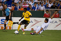 Victor Turcios (5) of El Salvador tries to tackle ball away from Lovel Palmer (14) of Jamaica at RFK Stadium in Washington, DC.  Jamaica defeated El Salvador, 2-0.