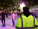 Manhattan, New York, U.S. 9th November 2013. A Security Guard in a neon jacket watches visitors ice skating, at Winter Village skating rink at Bryant Park that night.