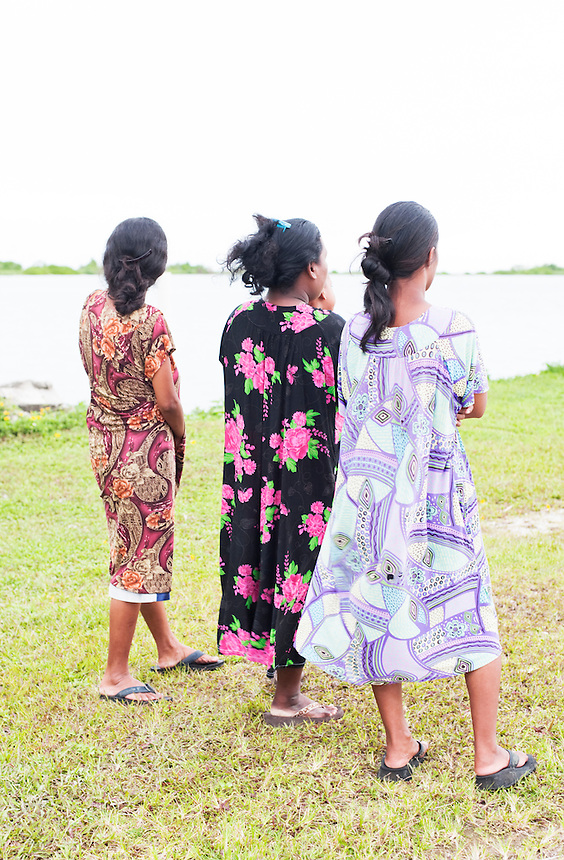 Three young women on Jaluit Atoll, looking towards the lagoon.