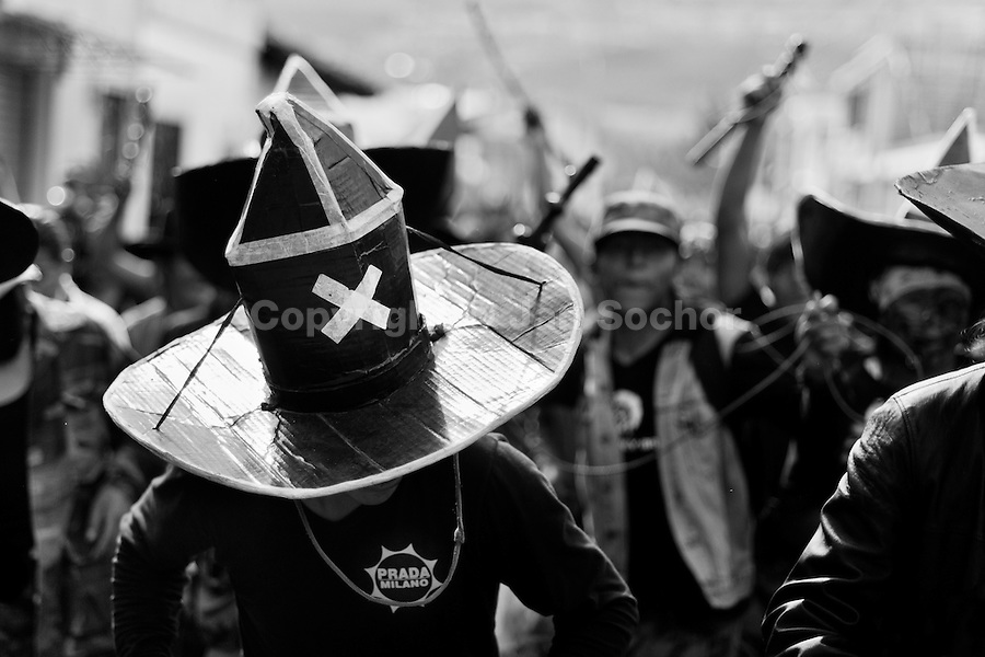 Indians, wearing black cardboard hats, dance wildly during the Inti Raymi (San Juan) festivities in Cotacachi, Ecuador, 24 June 2010. 'La toma de la Plaza' (Taking of the square) is an ancient ritual kept by Andean indigenous communities. From the early morning of the feast day, various groups of San Juan dancers from remote mountain villages dance in a slow trot towards the main square of Cotacachi. Reaching the plaza, Indians start to dance around. They pound in synchronized dance rhythm, shout loudly, whistle and wave whips, showing the strength and aggression. Dancers from either the upper communities (El Topo) or the lower communities (La Calera), joined in respective coalitions, seek to conquer and dominate the square and do not let their rivals enter. If not moderated by the police in time, the high tension between groups always ends up in violent clashes.