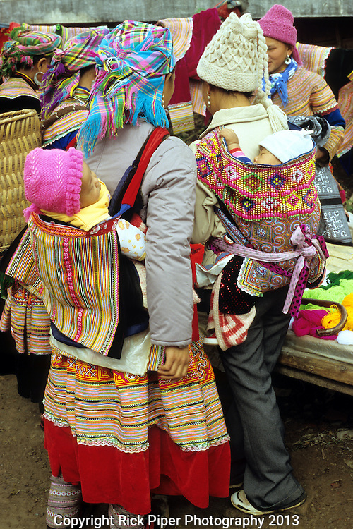 Flower Hmong Mothers And Babies - Flower Hmong mothers carrying their babies in traditional back carriers at the weekly market in the small town of Bac Ha, in the northwest of Viet Nam.