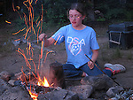 Girl at a campfire along the St. Croix River, Maine, USA