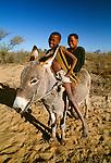 San youths on a donkey, Kalahari Desert, Botswana