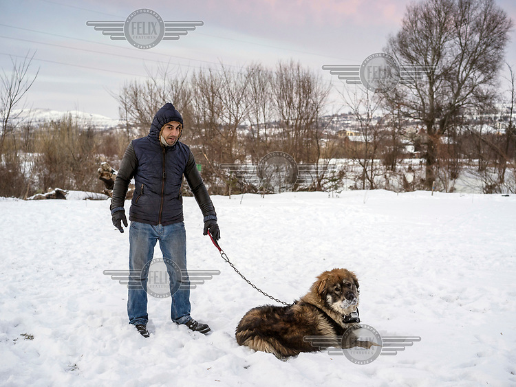 A young man stands outside in the snow with a dog.