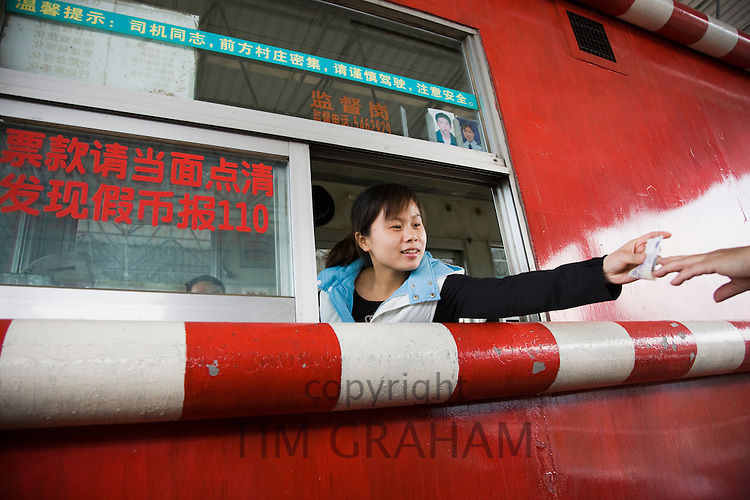 Woman in toll booth collecting payments, Guilin, China