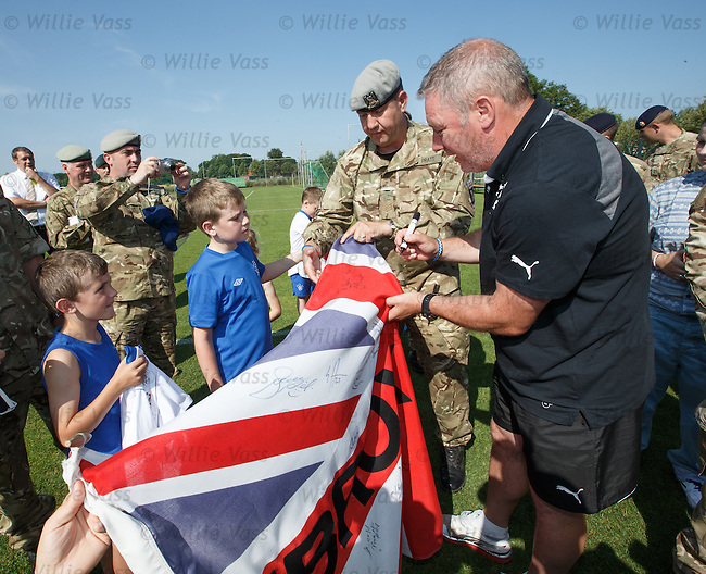 Rangers army visit in Germany - Ally McCoist autograps flags for the soldiers