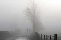 Two walkers in the mist on Little Bowland Road, Whitewell, Lancashire.
