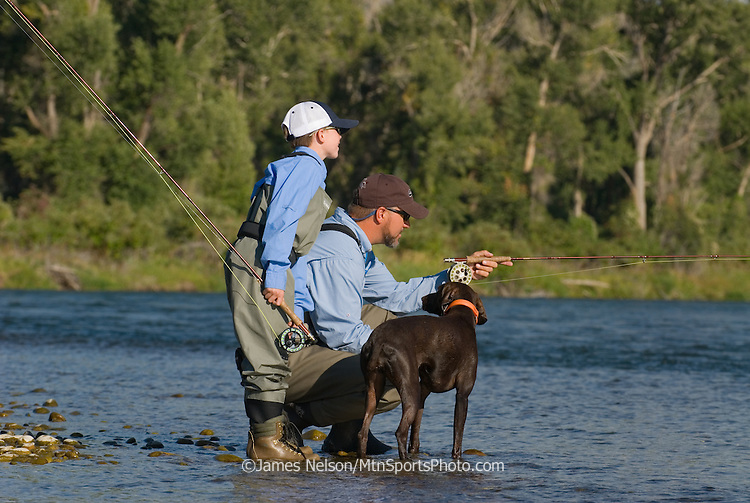 A father points out rising trout to his nine-year-old son, with a German short-hair pointer at their side, on the South Fork of the Snake River, Idaho.