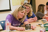 NWA Democrat-Gazette/FLIP PUTTHOFF <br /> Lindsey Evans (left) and Alexandra Wakelyn (cq) work on an experiment at the Scott Family Amazeum to complete an electric circuit that turns on a small fan.