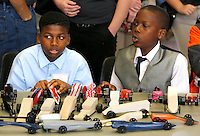 NWA Media/DAVID GOTTSCHALK - 12/12/14 - Dewayne White, left, and Braylin McKenzie, both seventh grade student at Mabelvale Magnet Middle School,  sit with CO2 propelled cars as they watch the dragster competition Friday December 12, 2014 at the Razorback Technology Challenge at the University of Arkansas in Fayetteville. More than 400 students from 28 middle schools, junior high schools and high schools in Arkansas, Oklahoma and Kansas participated and compete in the event that allowed them to show projects they have been working on  in technology and engineering education classes.