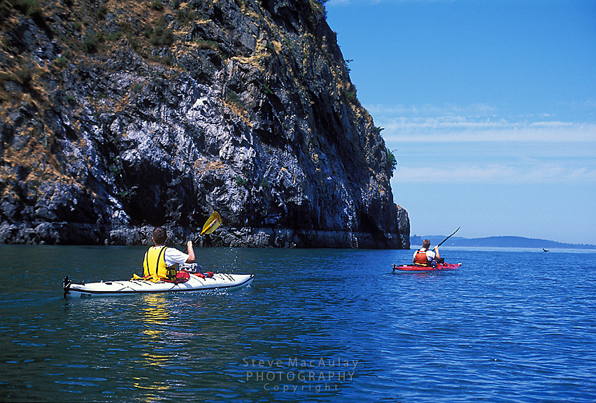 Two paddlers paddle along side a bluff, Guemes Island, San Juan Islands WA..MR on file