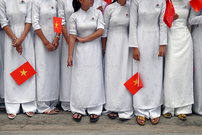 """Students dressed in the tradition """"ao dai"""", line the streets of Hoi An, Vietnam, during a parade for visiting Chinese delegates...Kevin German / LUCEO"""