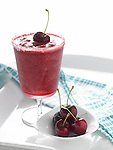 Blended Cherry Margarita on white tray with fresh whole cherries