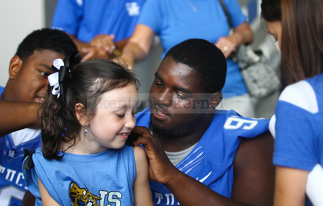 Senior defensive lineman Donte Rumph signs a young fans shirt during Fan Day on Friday, August, 9th, 2013 at Commonwealth Stadium in Lexington, KY. Photo by Michael Reaves | Staff