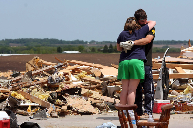 Cory Shepard hugs his wife, Kamie on the foundation of Cory's stepfather's destroyed home Monday, May 26, 2008 in Parkersburg.  They live in Parkersburg as well, but their home, on the opposite end of town, was spared.