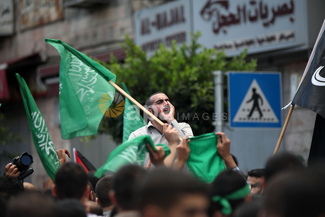 Palestinian protesters shout slogans and hold signs during a demonstration against Israel's military action and violence in the Gaza strip, in West Bank City of Ramallah July 20, 2014. Israeli strikes on Gaza on Sunday, July 20, 2014 killed 97 people, hiking the overall Palestinian death toll to 453 since the start of a major military campaign on July 8, health officials said. Photo by Shadi Hatem