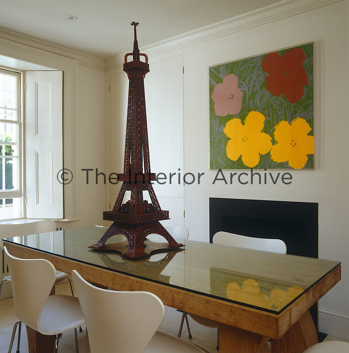 An Andy Warhol print hangs above the fireplace in the dining room and a model of a tower dominates the glass-topped table