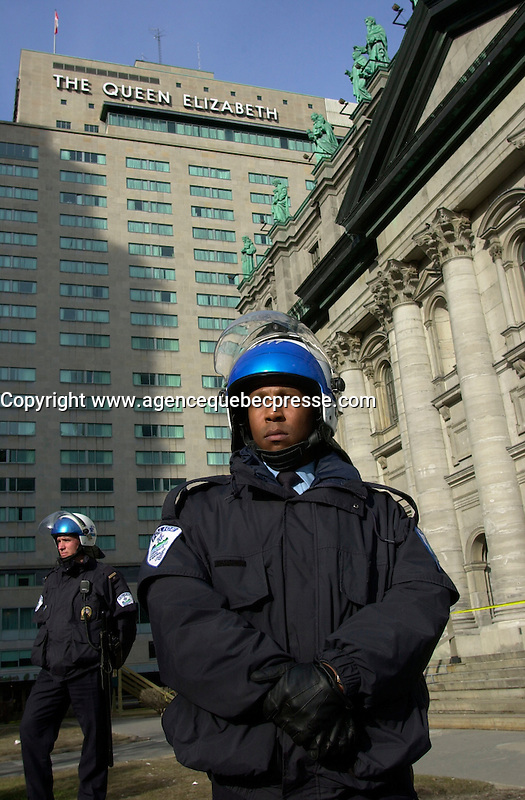 Montreal, April 17, 2001<br /> <br /> One of the hundreds of Montreal policemen securing the area around  the<br /> Queen Elizabeth Hotel where the `` Conference of Montreal `` on economy globalization is beeing held until April 19th 2001 look quietly at a<br />  group of demonstrators opposed to the Free Trade Area of the Americas (FTAA) on April 17, 2001 in downtown Montreal (Quebec, CANADA).<br /> <br /> The  conference feature speakers such as Mexico President Foxx and New York Governor Pataki.