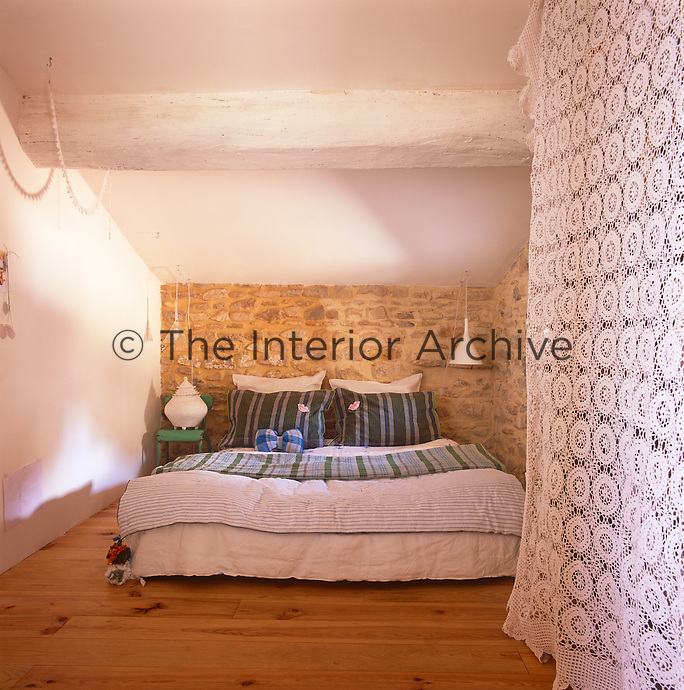 A simple, rustic style bedroom with a beamed ceiling and a wooden floor. A double bed is placed against an exposed stone wall.