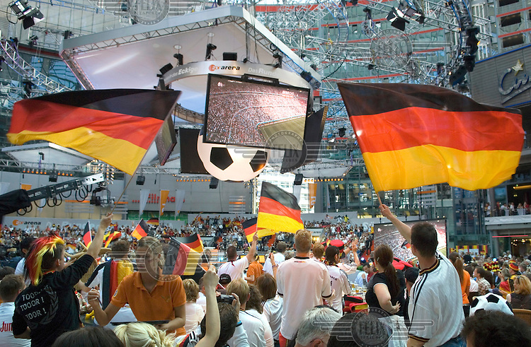 German fans watch live television coverage of a football match in the 2006 World Cup at a public screening inside the Sony Centre.