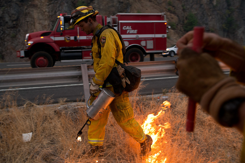 Firefighters use drip torches and fusees to burn excess brush, creating a wide fire break along US Route 50 near the town of Pollock Pines, California, USA, on 18 September 2014. Fire crews around California fight 12 major fires across the state, including the King Fire, located 56 miles (90 kilometers) east of Sacramento, California, which more than doubled in size overnight to 70,994 acres (28,730 hectares) and 5% contained.