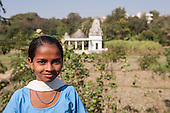India; road from Udaipur to Jodhpur. Girl in school uniform by a temple.