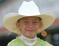 A young girl wearing a white cowboy hat smiles before entering the ring for a horse competition at the Knox County Fair in Mt. Vernon, Ohio.<br />