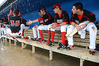 Batavia Muckdogs shortstop Javier Lopez (35), with teammates Connor Burke, J.T. Riddle (5), Justin Bohn (56) and Austin Dean (3) looking on,  uses the rafter to help get down dugout after it flooded during a brief but heavy rain storm during a game against the Hudson Valley Renegades on August 8, 2013 at Dwyer Stadium in Batavia, New York.    The game was called due to unplayable field conditions.  (Mike Janes/Four Seam Images)