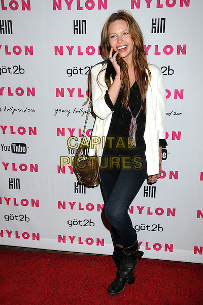DAVEIGH CHASE.Nylon Magazine's Young Hollywood Party held at the Roosevelt Hotel's Tropicana Bar, Hollywood, California, USA..May 12th, 2010.full length black suit jacket blazer jeans denim white cream top necklace hand smiling brown bag purse .CAP/ADM/BP.©Byron Purvis/AdMedia/Capital Pictures.