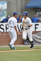 Asheville Tourists shortstop Brendon Rodgers (1) is congratulated by manager Warren Schaeffer (13) after hitting a home run during game one of a double header against the Charleston RiverDogs at McCormick Field on July 8, 2016 in Asheville, North Carolina. The RiverDogs defeated the Tourists 10-4 in game one. (Tony Farlow/Four Seam Images)