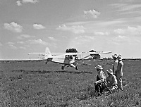 A group fo men watches as a vinage airplane buzzes a field .  (Photo by bcpix.com)