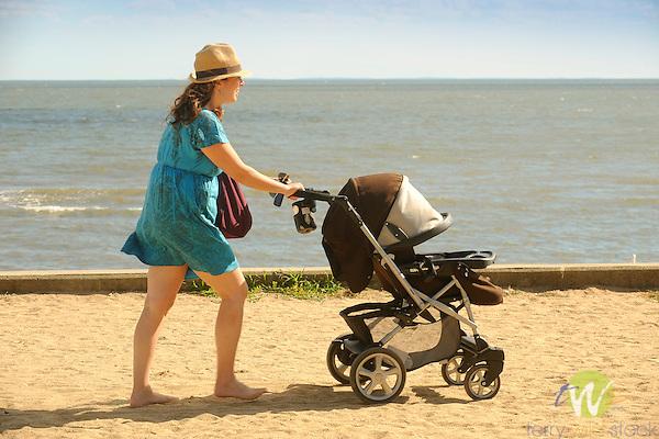 Garvin Beach Park, Madison, CT. Woman pushing baby carriage.