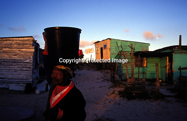 ditown00283.Digital. Townships. An unidentified woman fetching water at a water tap as the suns sets on November 7, 2003 in a poor area of Site B, Khayelitsha, South Africa.  Woman balancing bucket of water on head, lifestyle, poverty, environmental issues, water. .©Per-Anders Pettersson/iAfrika Photos