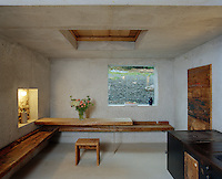 A long pine bench runs around two walls of the kitchen with a table at one end