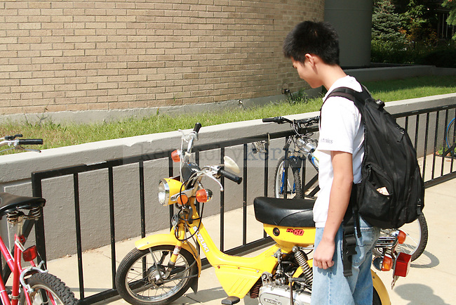 Duy Tran a chemistry senior climbs aboard mo-ped outside the chemistry physics building Tuesday afternoon. Photo by LeeAlan Yates   Staff.