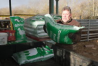 Shepherd lifting bags of sheep compound into the back of an ATV<br /> &copy;Tim Scrivener Photographer 07850 303986<br /> ....Covering Agriculture In The UK....