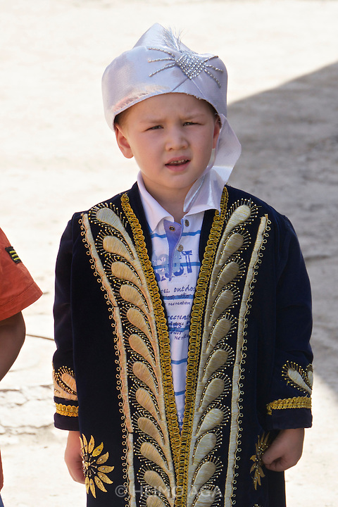 Uzbekistan, Khiva. Boy in festive traditional clothes waiting for his circumcision.