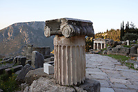 DELPHI, GREECE - APRIL 11 : A detail of a fluted Ionic column with capital on the Sacred Way with the Treasury of the Athenians in the background at sunrise, on April 11, 2007 in the Sanctuary of Apollo, Delphi, Greece. (Photo by Manuel Cohen)