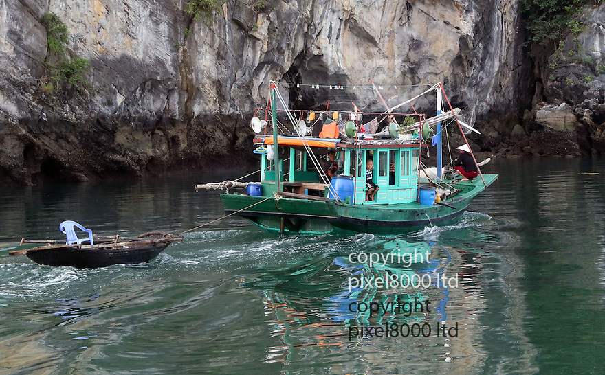Pic shows: Little boy Chelsea fan in full kit on traditional Vietnamese fishing boat in Ha Long Bay, South China Sea early today.<br /> <br /> <br /> <br /> He seems to be contemplating the Blues 2-2 draw as his mother repairs fishing net at the front of the boat.<br /> <br /> The family eke out a small income from catching fish but somehow have afforded enough to buy a replica kit for their son.<br /> <br /> The multi-billion pound English Premier League is big business even in poor South East Asian Countries.<br /> <br /> Although heartening for Louis Van Gaal  the washing line reveals the presence of a Manchester United fan on board<br /> <br /> <br /> (Halong Bay is one of the eight natural wonders of the world, with nearly 2000 tiny islands.)<br /> <br /> <br /> <br /> Pic by Gavin Rodgers/Pixel 8000 Ltd