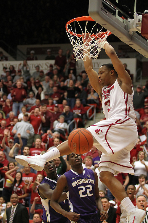 Reggie Moore (#3), Washington State sophomore point guard, skies to the hoop for a thunderous alley-oop dunk off of a feed from Faisel Aden during the Cougars 87-80 Pac-10 conference victory over arch-rival Washington at Friel Court at Beasley Coliseum in Pullman, Washington, on January 30, 2011.
