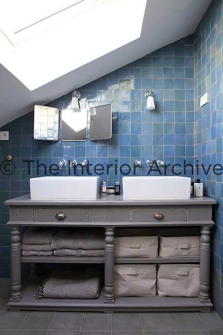 This attic bathroom is furnished with an antique wooden washstand supporting a pair of contemporary wash basins in a tiled alcove