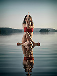 Artistic concept of a young woman in swimsuit doing a variation of yoga Eagle posture, Guradasana, meditating on a floating platform in water on the lake in sunrise. Muskoka, Ontario, Canada.
