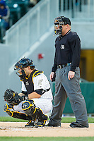 Charlotte Knights catcher Josh Phegley (4) sets up behind the plate as umpire Jonathan Bailey looks on during the International League game against the Gwinnett Braves at BB&T Ballpark on April 16, 2014 in Charlotte, North Carolina.  The Braves defeated the Knights 7-2.  (Brian Westerholt/Four Seam Images)